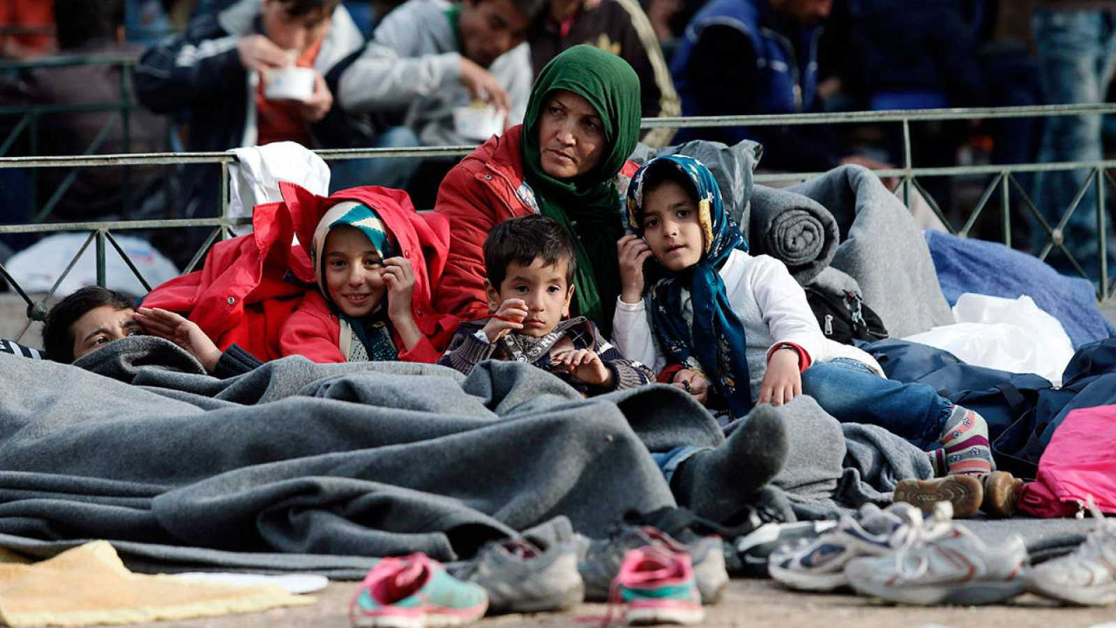 Una refugiada espera con varios niños en Atenas