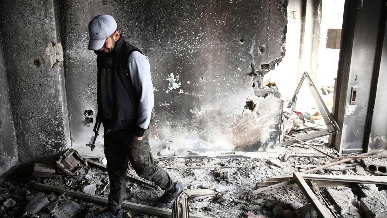 Un soldado sirio opositor camina sobre las ruinas de una vivienda destruida en Damasco