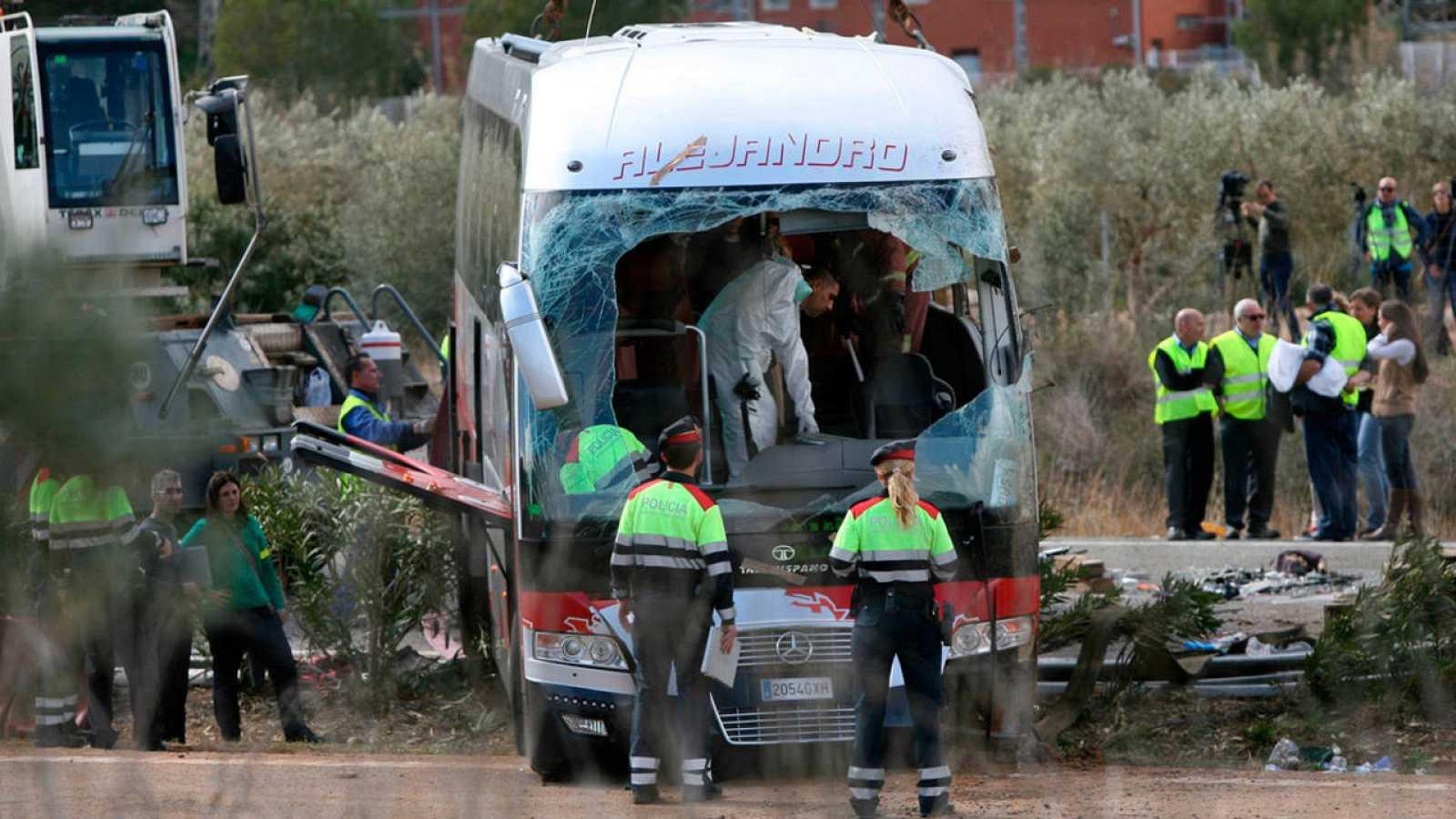Agentes de los Mossos d'Esquadra junto al autocar accidentado en la AP-7 a la altura de Freginals (Tarragona).
