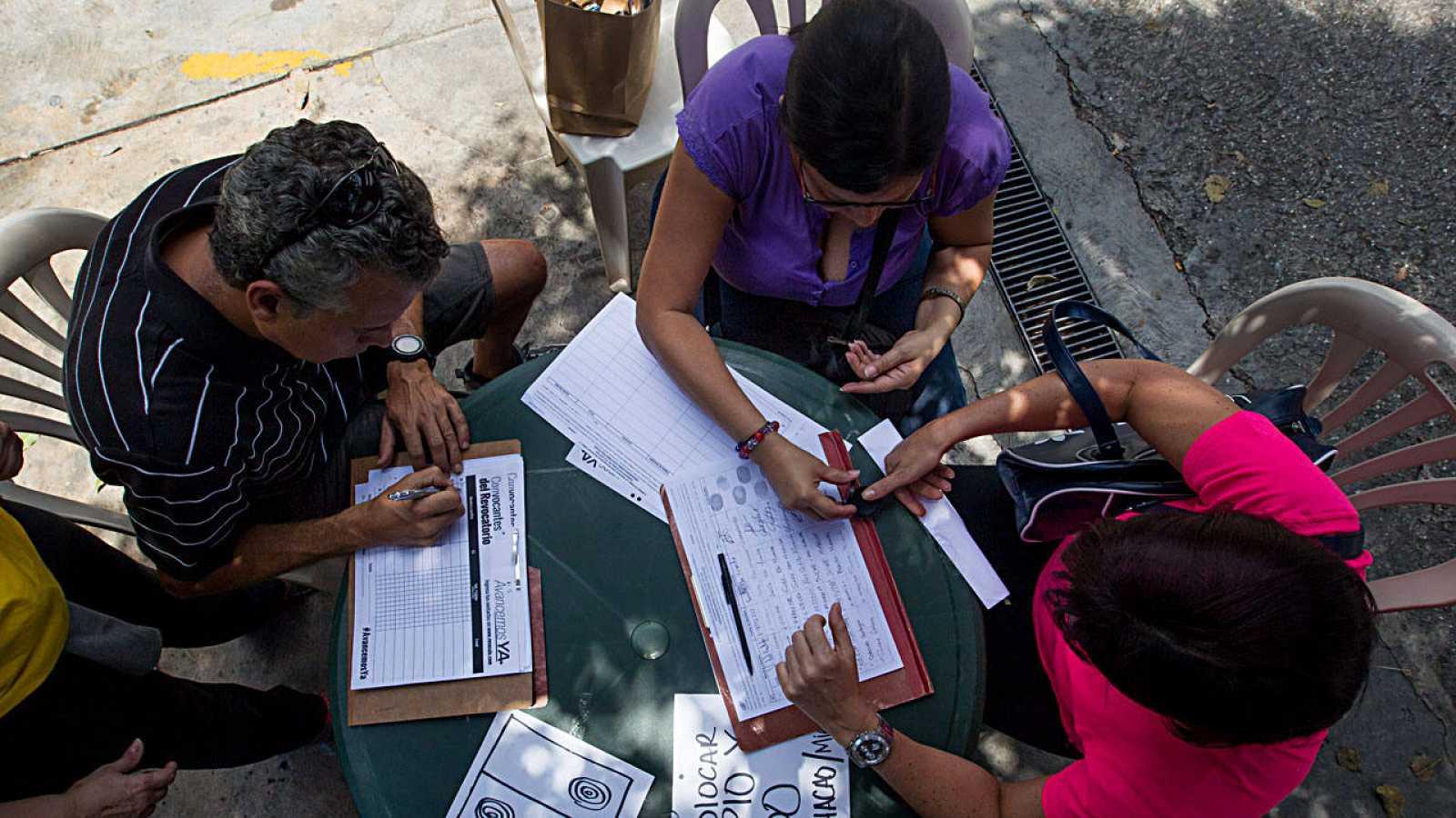 Un grupo de personas recoge firmas para el referéndum revocatorio contra Nicolás Maduro en Caracas