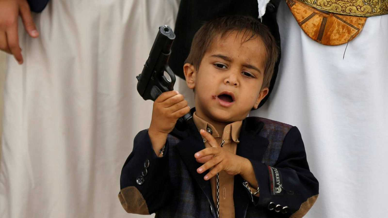 Un niño sujeta la pistola de su padre en una concentración de hutíes en Sana