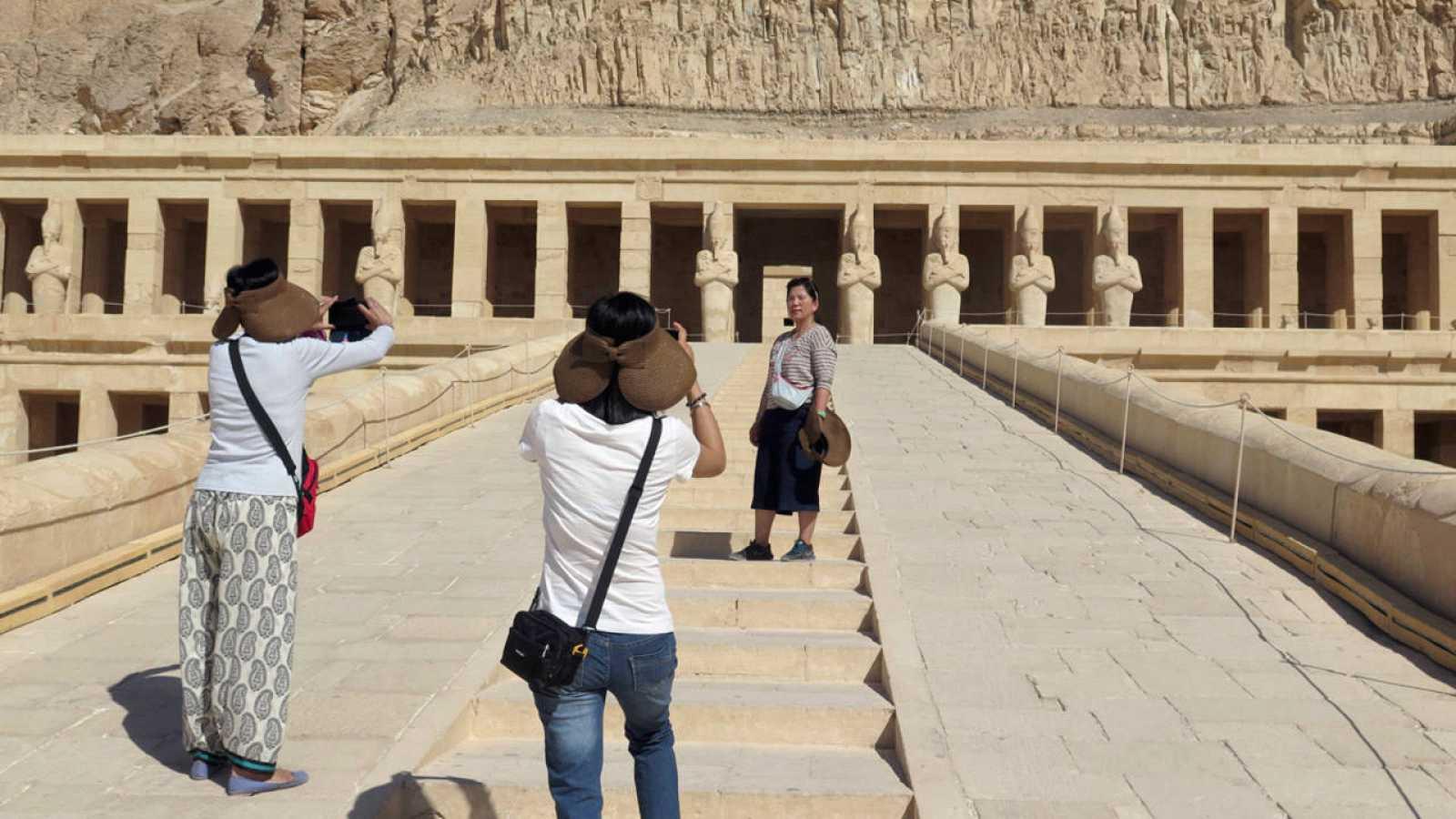 Turistas de nacionalidad china se hacen fotos frente al templo de Hatshepsut, en Luxor