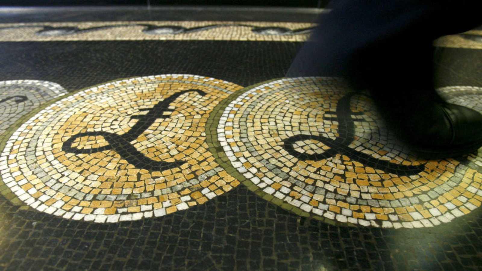 Una persona camina sobre un mosaico con el símbolo de la libra siutado en la entrada del Banco de Inglaterra