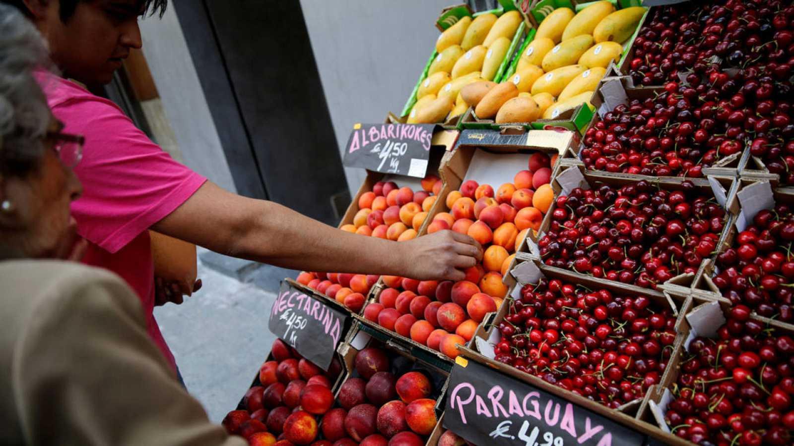 Una anciana compra fruta en Madrid