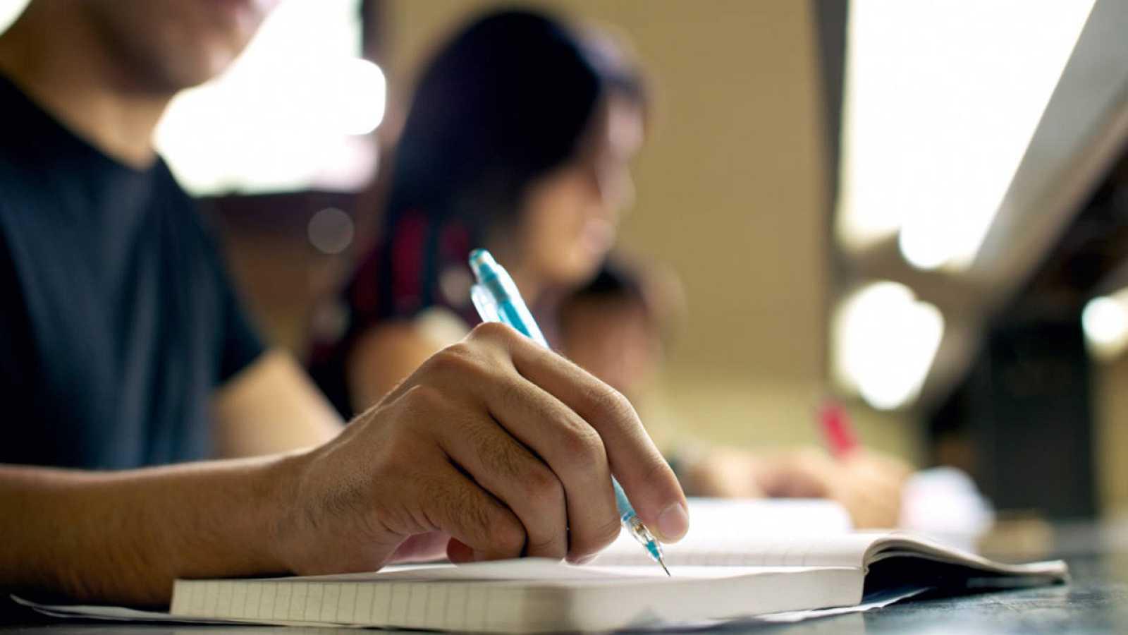 Un estudiante toma notas en clase