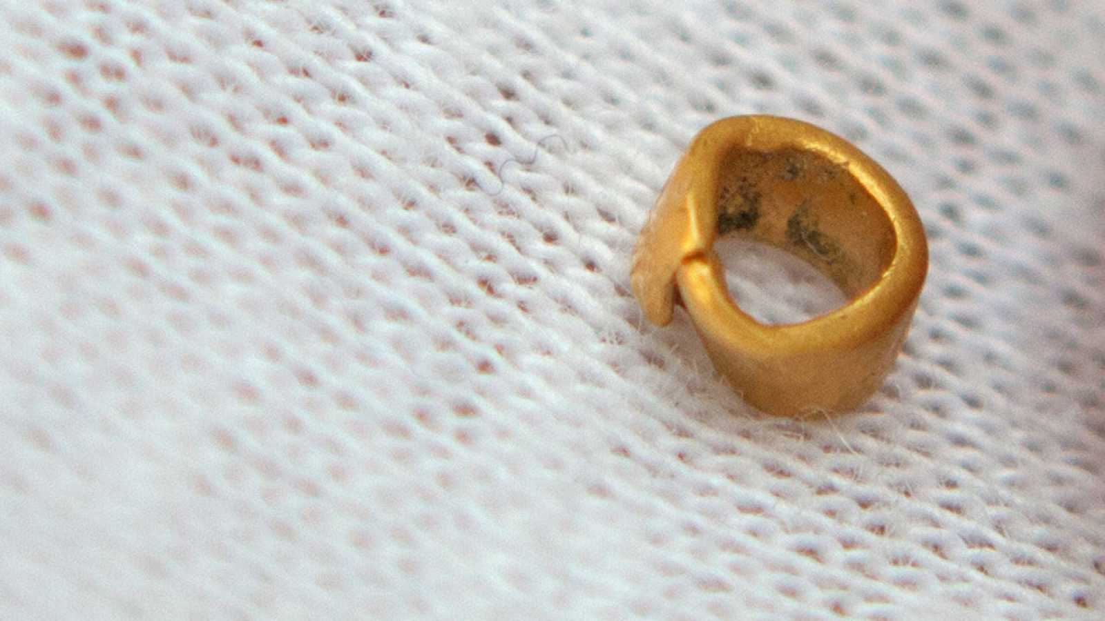 El objeto de oro hallado parece un abalorio.