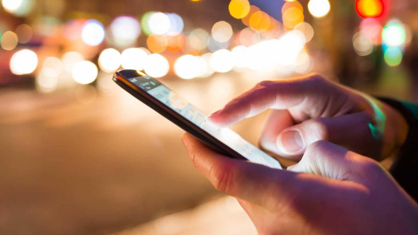 Una persona utilizando su teléfono móvil en la calle