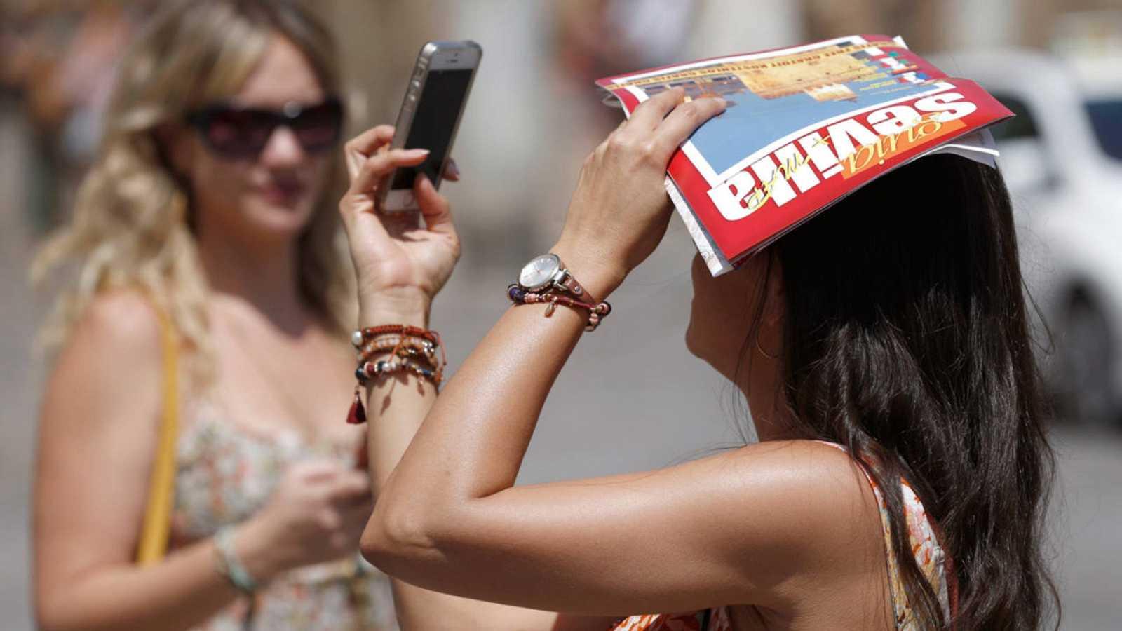 Una turista se fotografía con su teléfono móvil mientras se proteje del sol con una guía turística de Sevilla