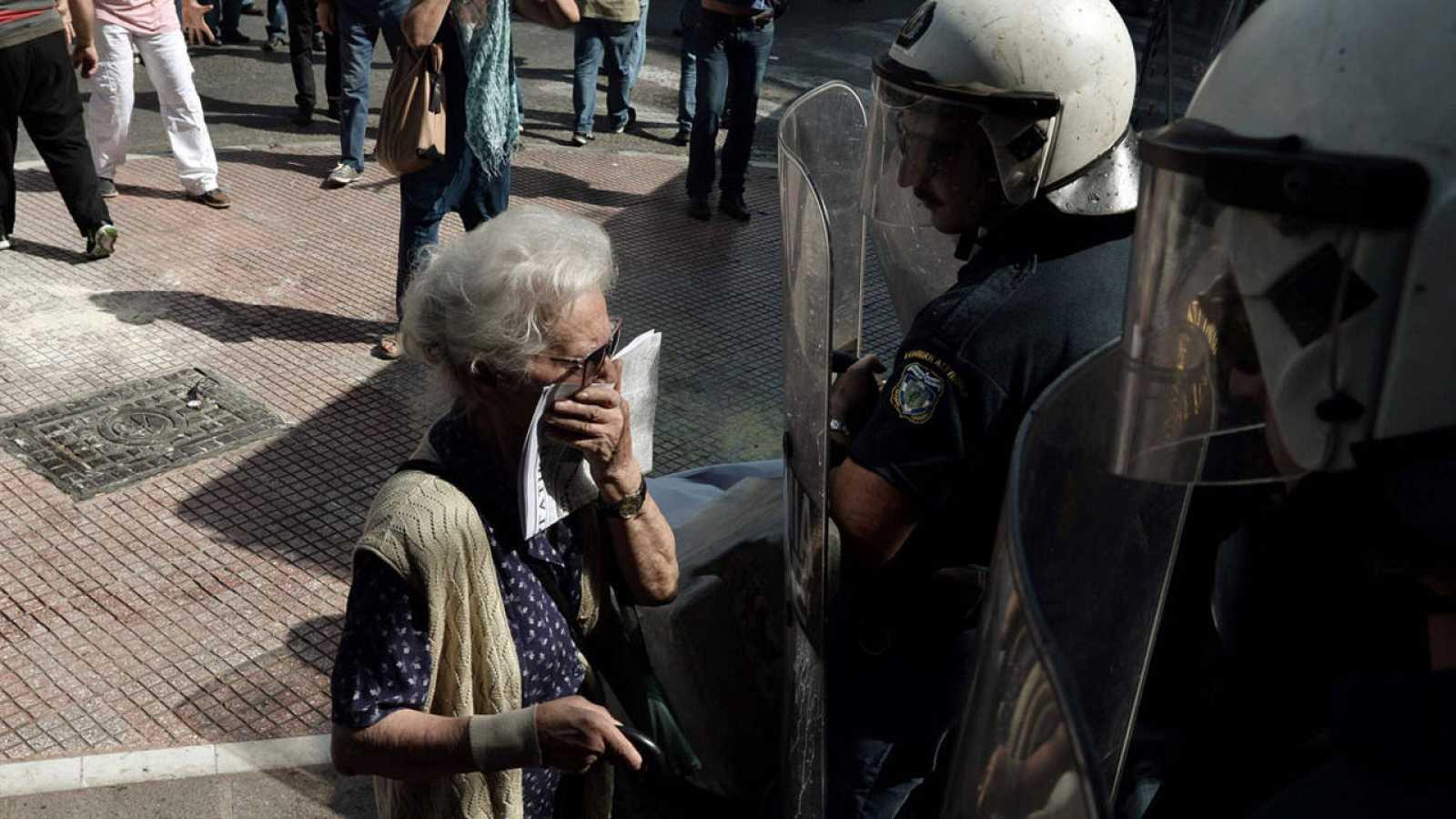 Una pensionista griega intenta respirar a través de un pañuelo frente a los antidisturbios