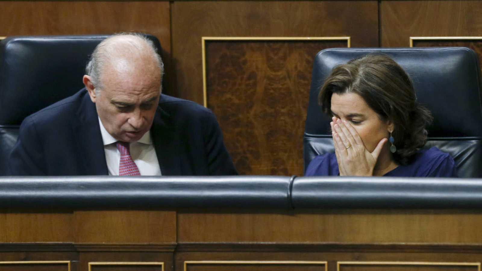 El ministro del Interior en funciones, Jorge Fernández Díaz, y la vicepresidenta del Gobierno en funciones, Soraya Sáenz de Santamaría, durante el pleno del Congreso