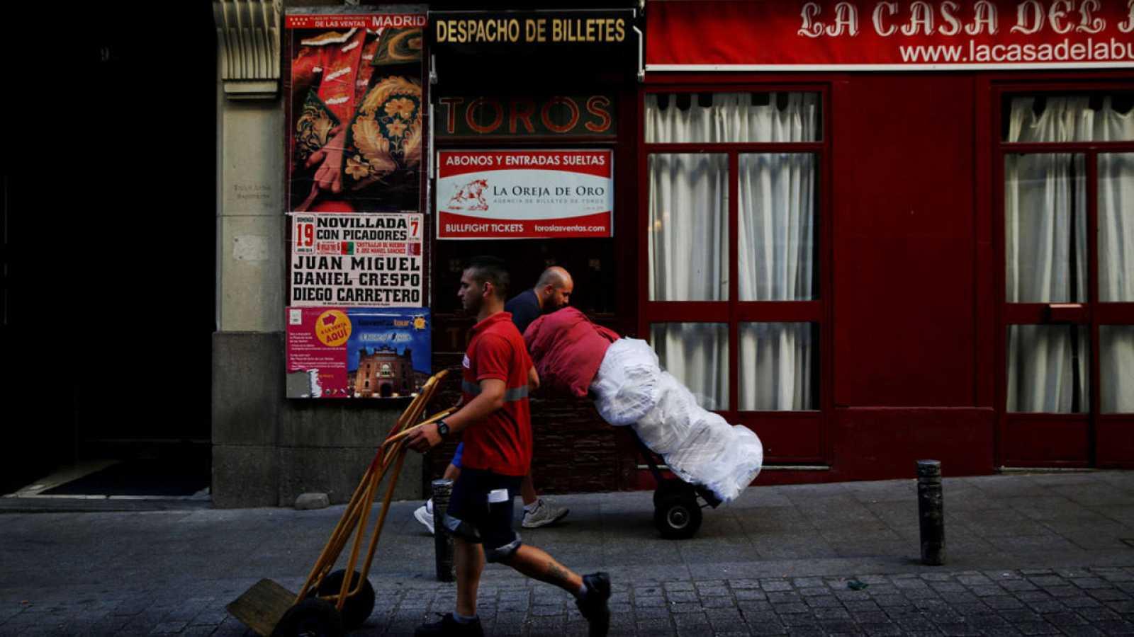 Dos operarios trasladan mercancía con carretillas en el centro de Madrid
