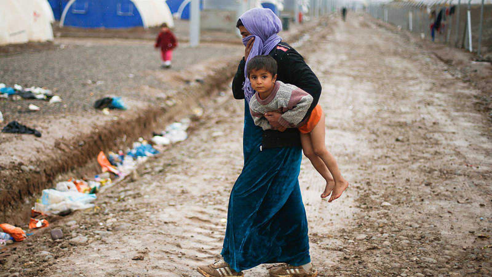 Una mujer sostiene a su hijo en uno de los campamentos para los refugiados huidos de Mosul