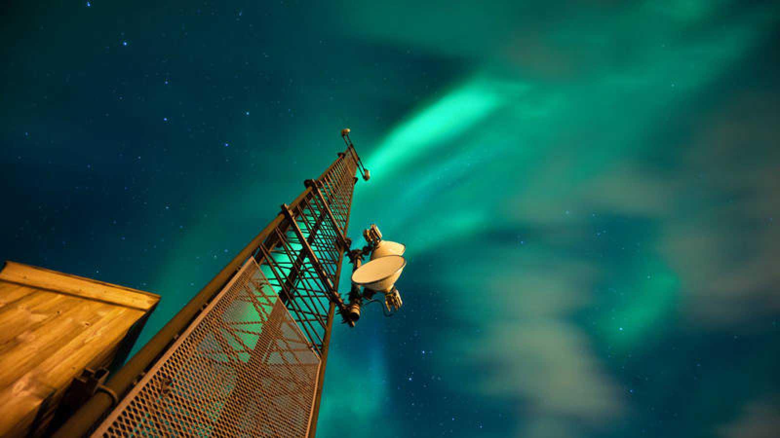Una torre de telecomunicaciones iluminada por una aurora boreal
