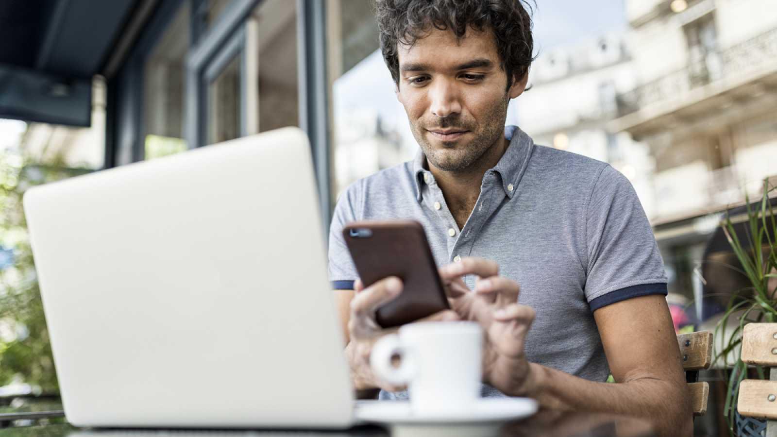 Un hombre trabaja con su ordenador y su teléfono móvil desde una cafetería.