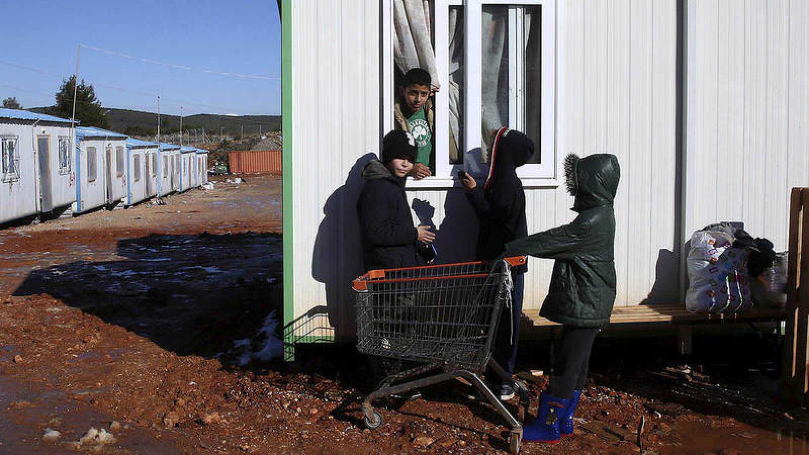 Niños refugiados hablan en el barracón donde viven en el campamento de refugiados de Malakasa, a 60 kilómetros de Atenas, Grecia
