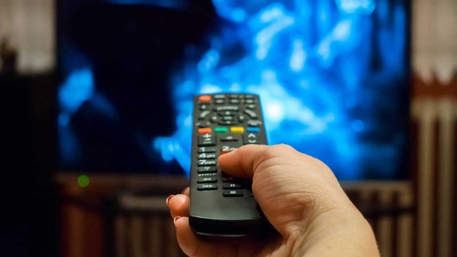 Una persona cambia de canal en su televisor.