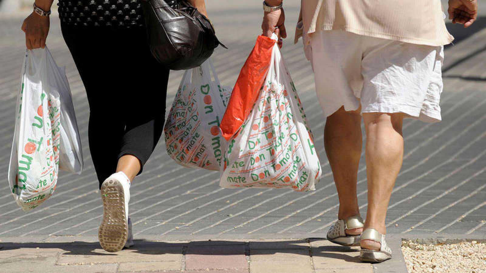 Dos mujeres llevan bolsas de plástico tras realizar unas compras.