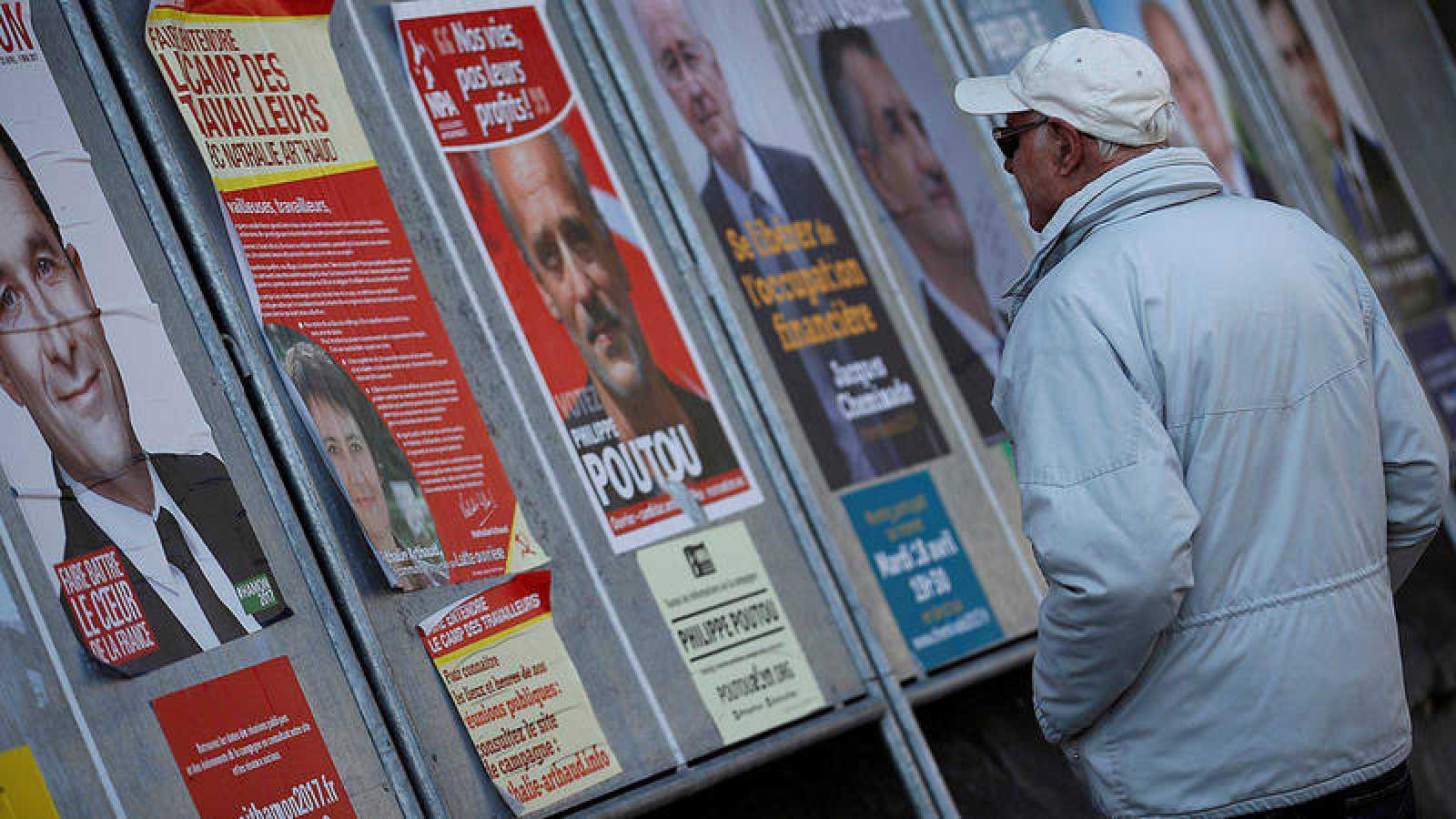 Un hombre pasa junto a carteles electorales en Enghien-les-Bains, cerca de París, Francia