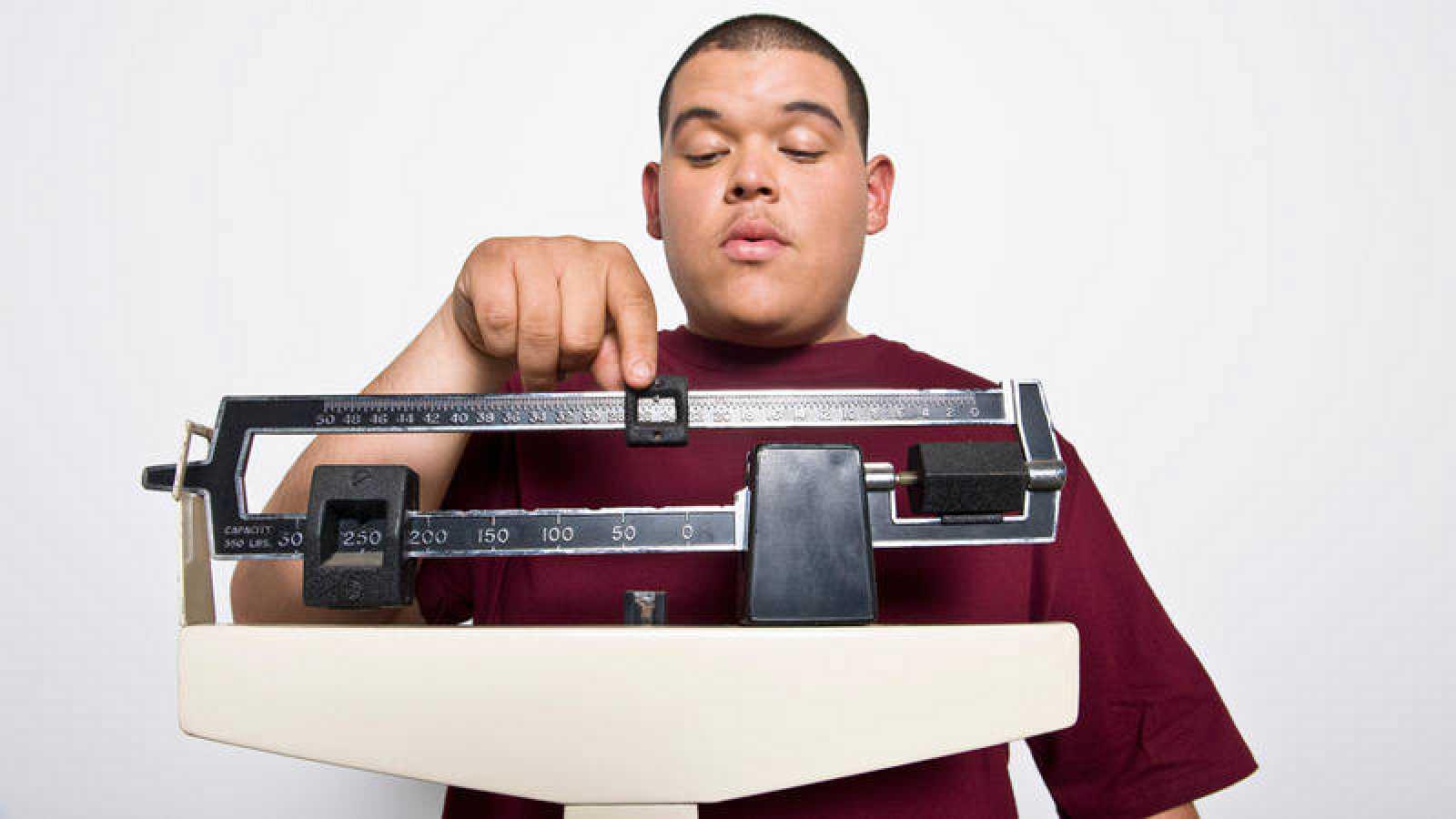 Obesidad - Un hombre joven pesándose en una báscula