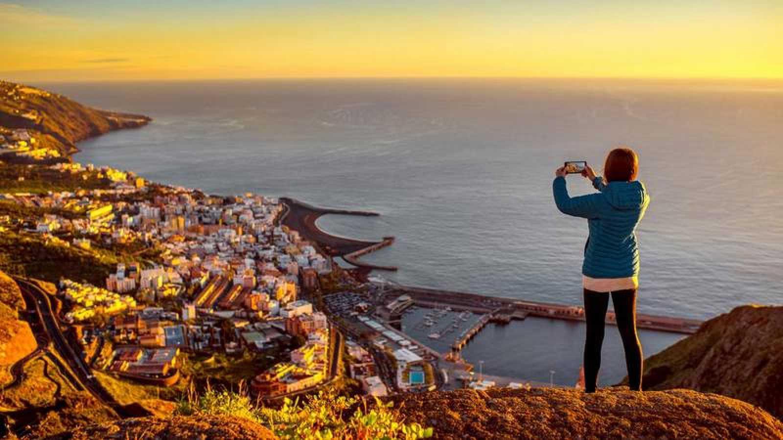 Una joven obtiene una fotografía con su teléfono móvil de Santa Cruz de la Palma.