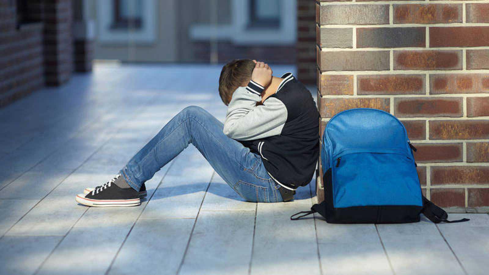 Un niño víctima de acoso escolar, sentado en el suelo del colegio