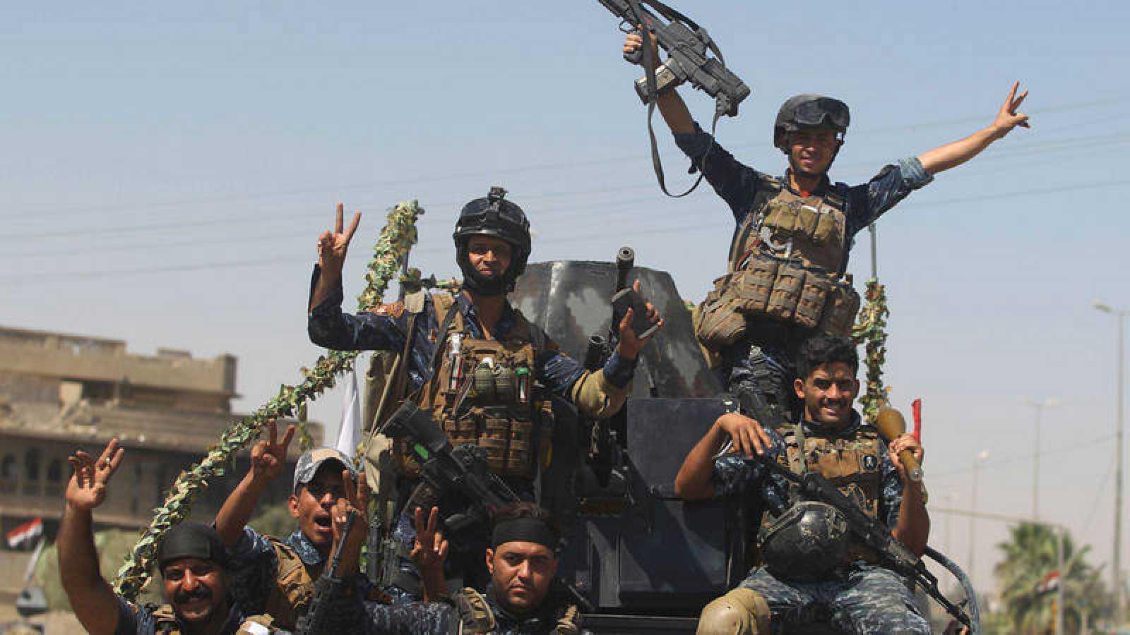 Miembros de la policía federal iraqui hacen el gesto de la victoria en la Ciudad Vieja de Mosul.