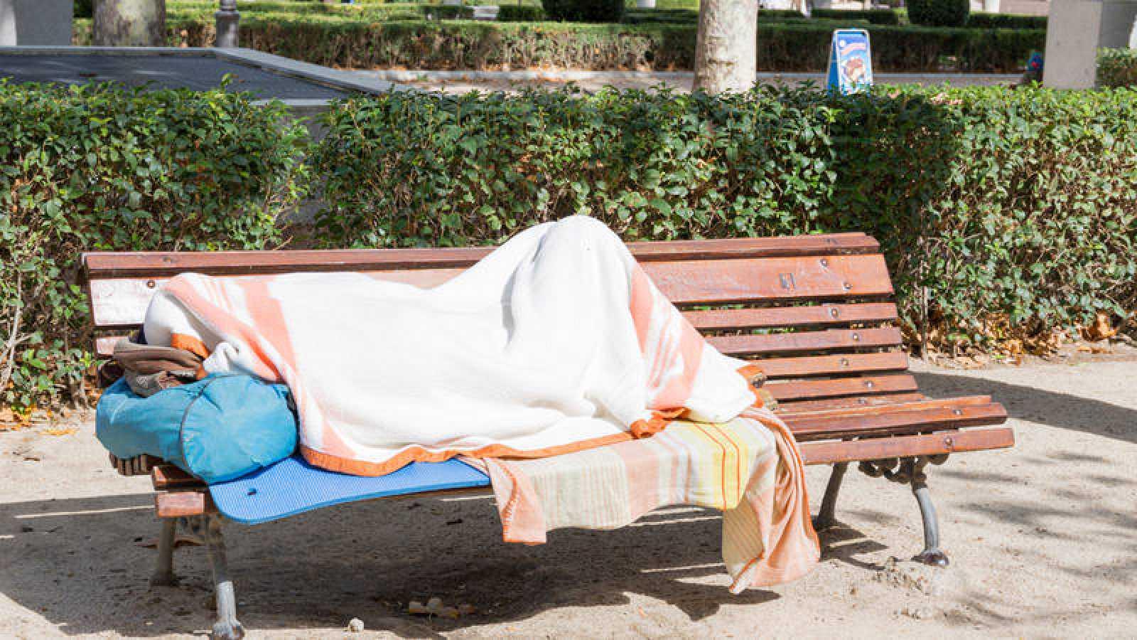 Un indigente duerme en un parque de Madrid