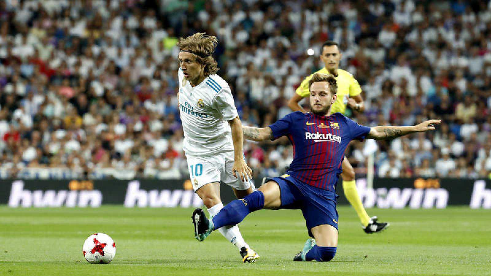 Modric trata de conducir el balón ante Rakitic en un momento del partido