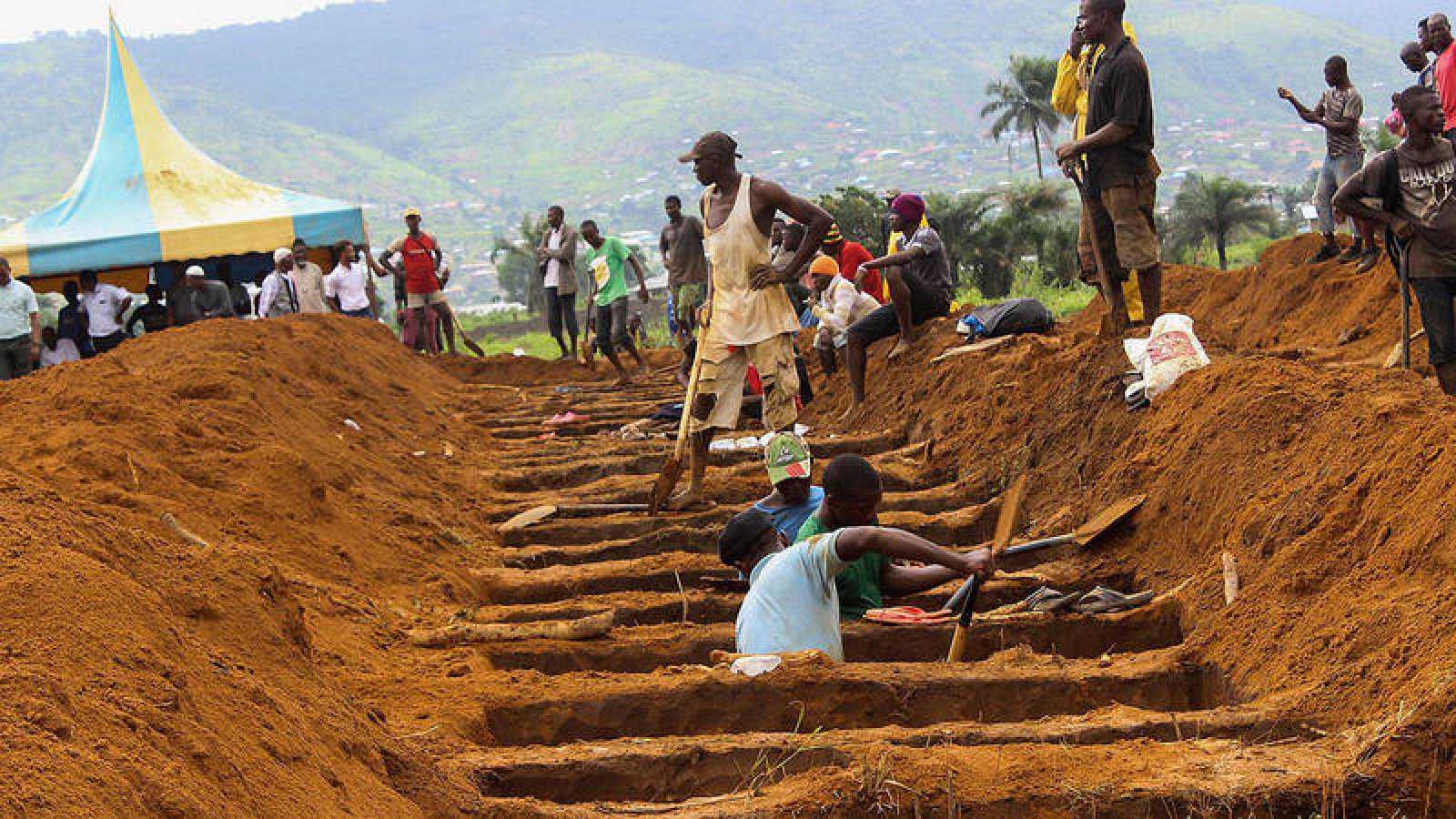Varios operarios caban fosas comunes para víctimas mortales de inundaciones y corrimientos de tierra en Waterloo (Sierra Leona)