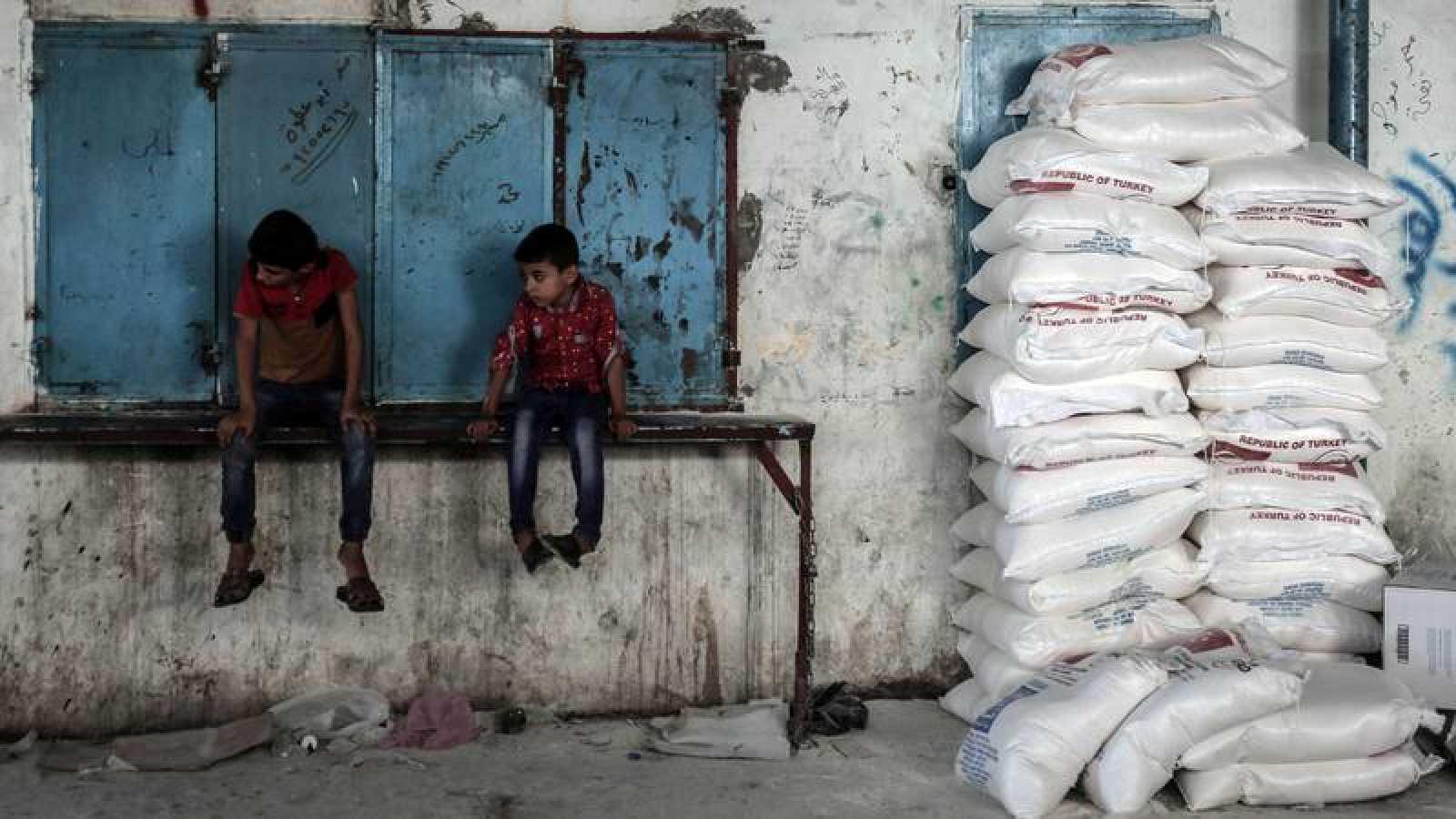 Dos niños gazatíes esperan sentados al lado de sacos de comida provenientes de la ayuda humanitaria de Agencia de Naciones Unidas para los Refugiados de Palestina en Oriente Próximo.