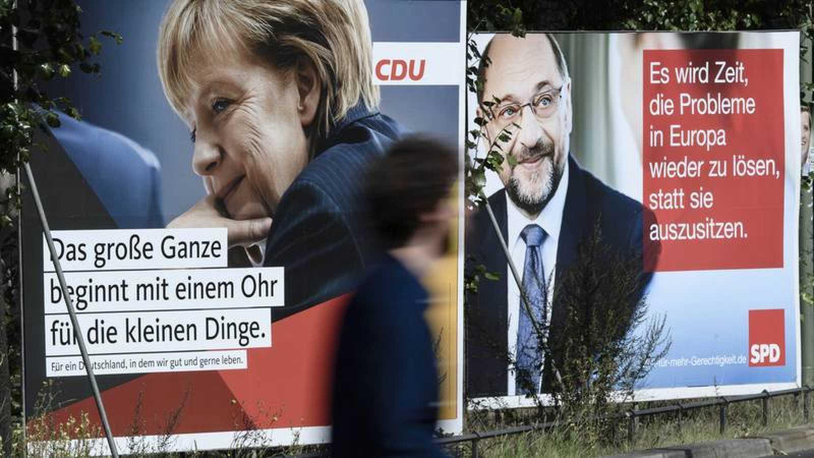 Carteles electorales que muestran a la candidata de la CDU, Ángela Merkel, y al del SPD, Martin Schulz