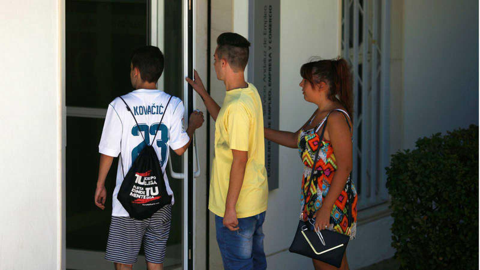 Tres jóvenes se disponen a entrar en una oficina de empleo en Ronda