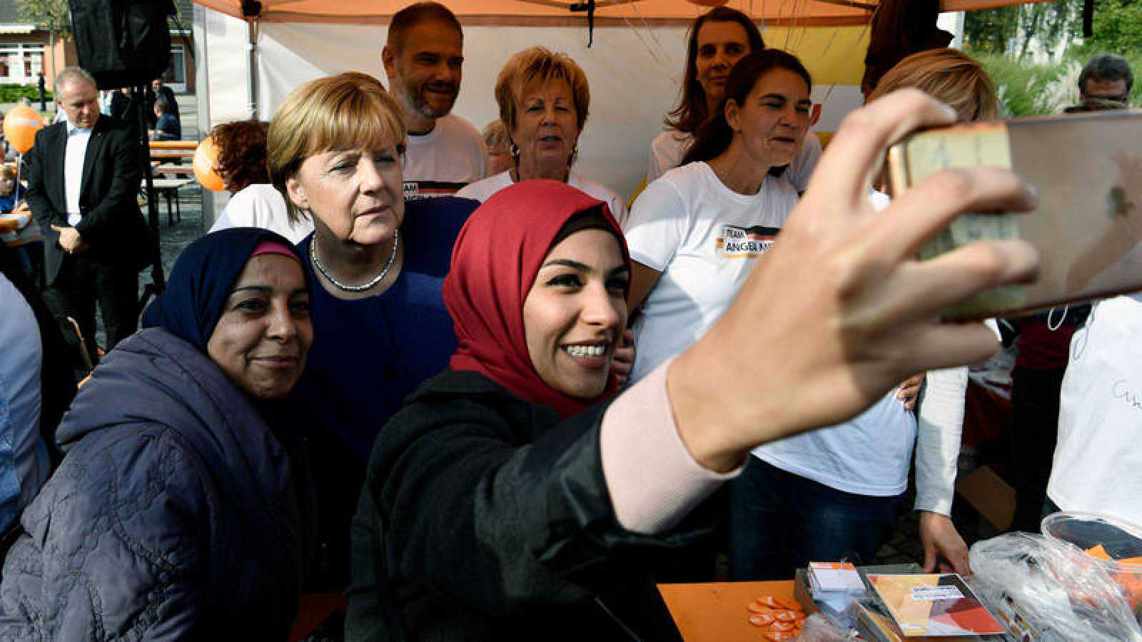 Una refugiada siria posa para un selfie con Angela Merkel