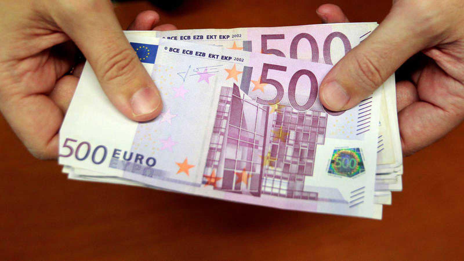 Un empleado de banca muestra varios billetes de 500 euros