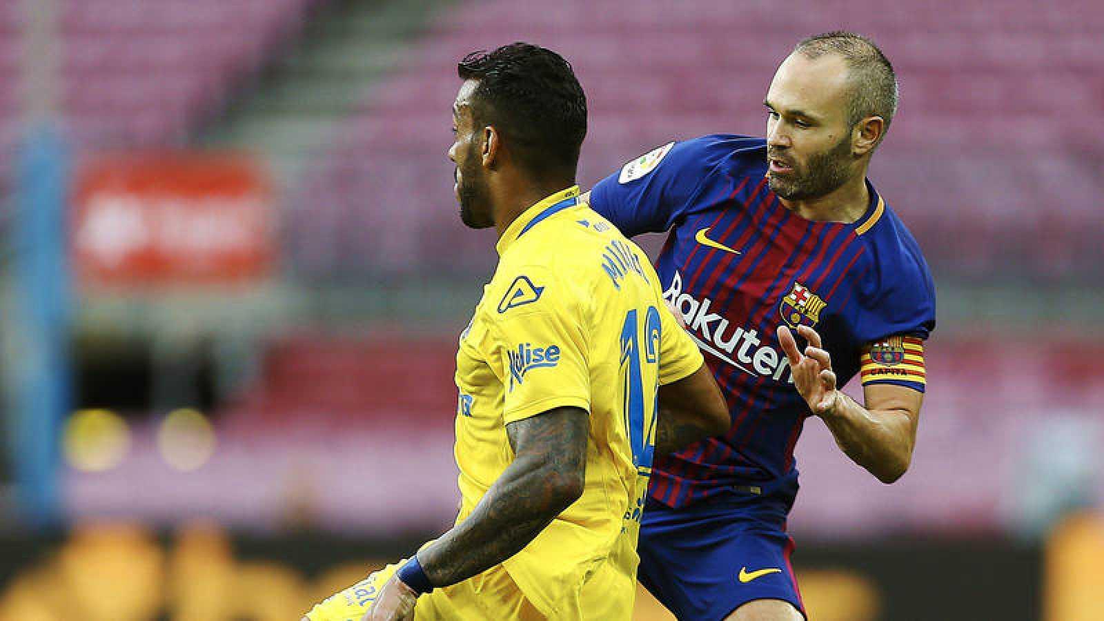 Iniesta disputa un balón con el jugador de Las Palmas Míchel Macedo.