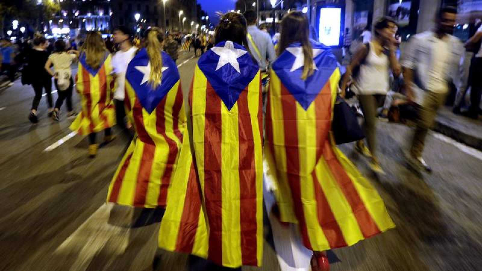 Varias jóvenes con banderas esteladas caminan por plaza de Catalunya