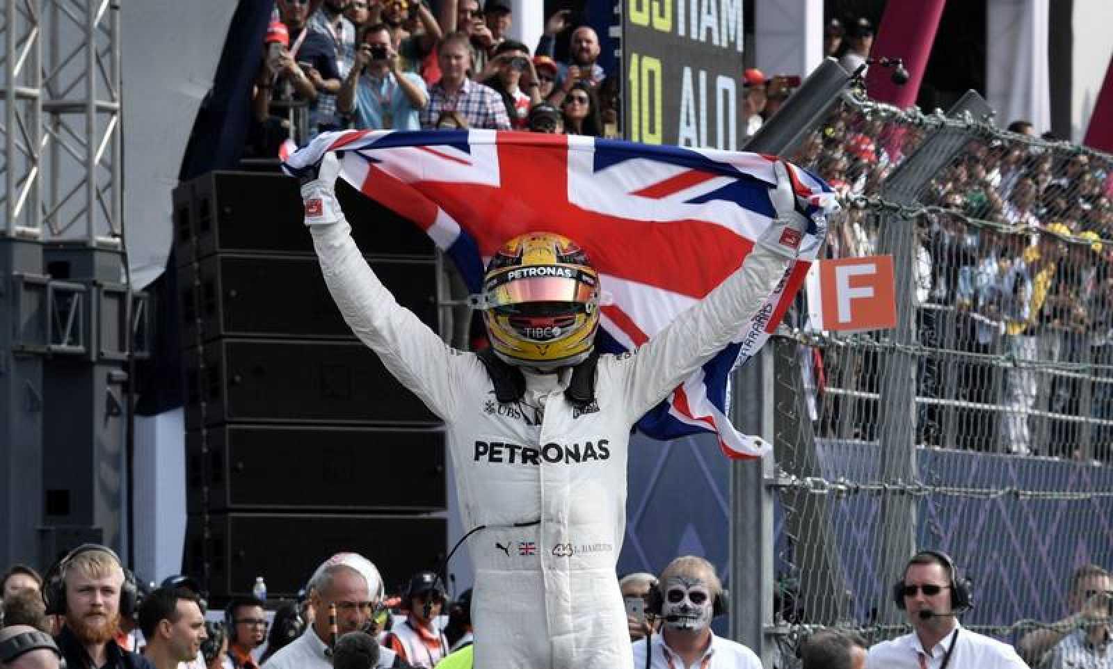 Hamilton celebra su cuarto mundial de F1 tras bajarse del Mercedes.