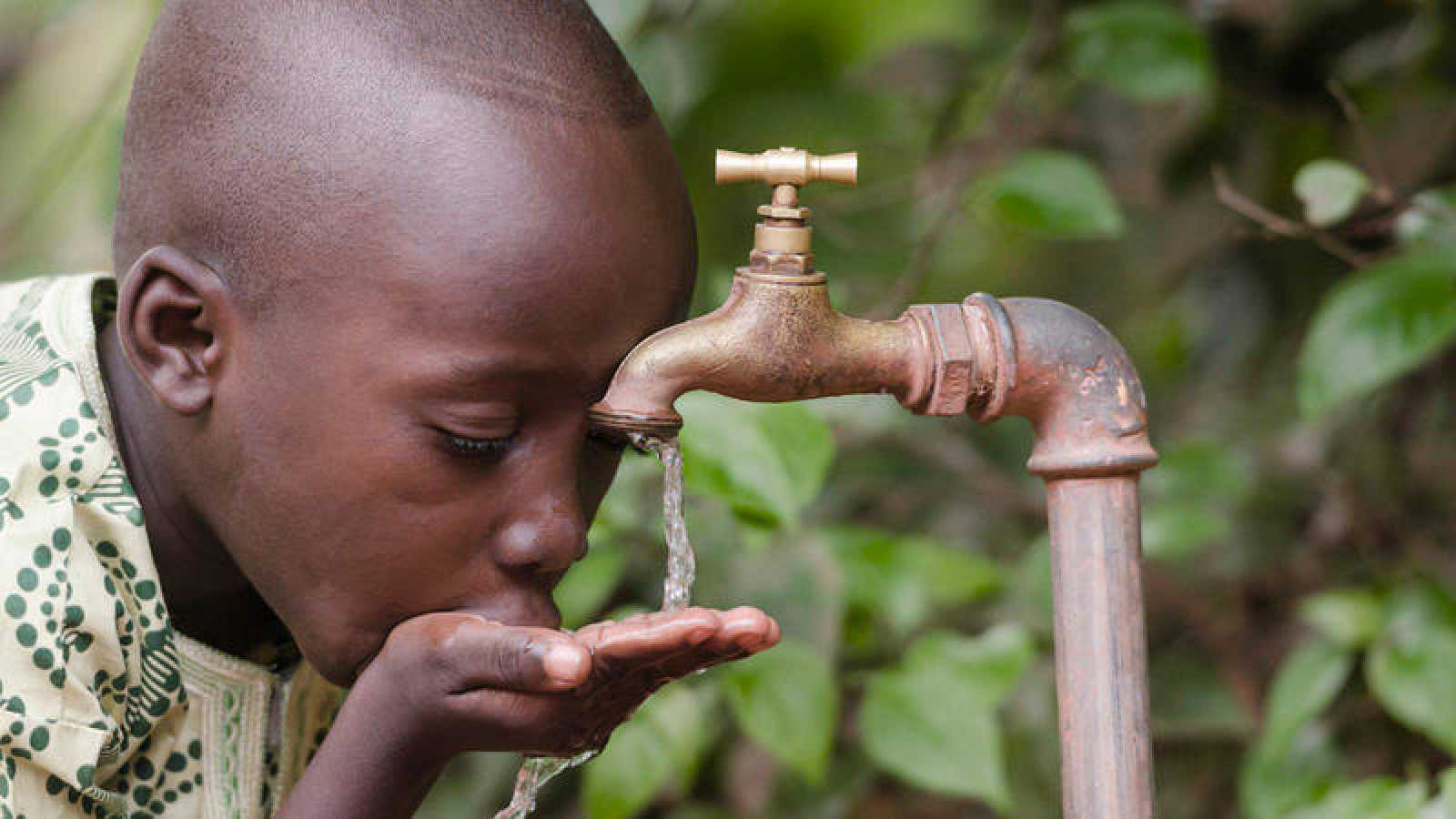 Un niño africano bebe en un grifo agua no potable