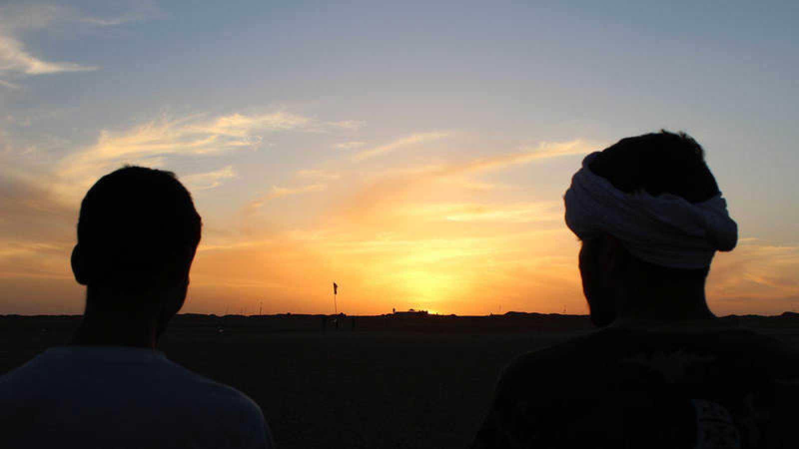 Dos jóvenes saharauis observan el muro que separa el Sáhara Occidental.