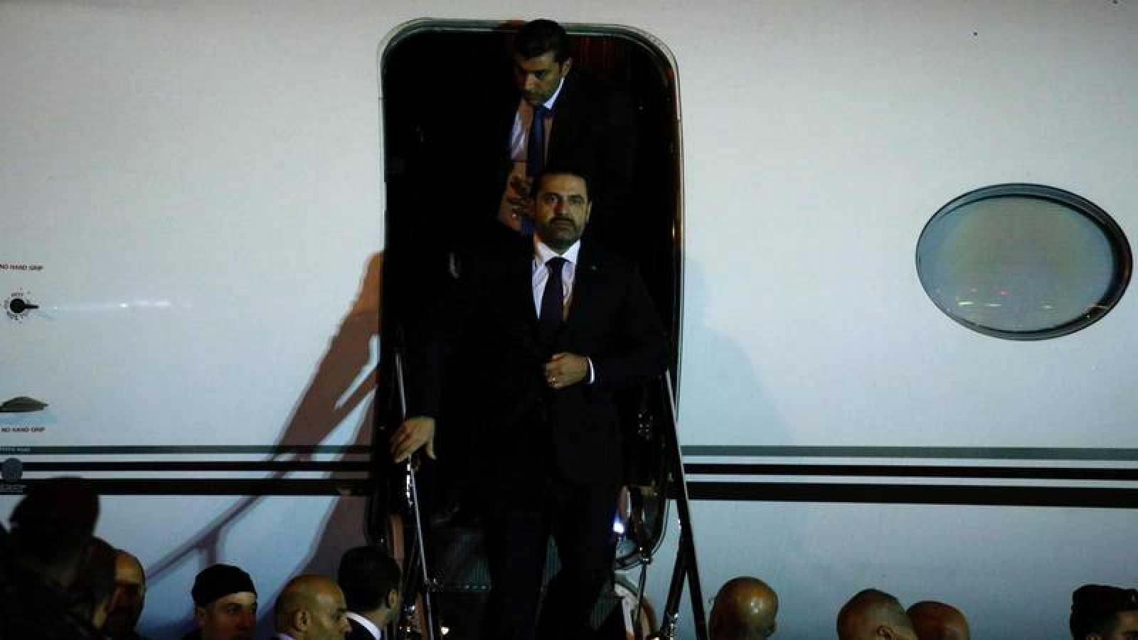 El primer ministro dimisionario de Líbano, Saad al-Hariri, desciende por las escalerillas del avión en el aeropuerto de Beirut.