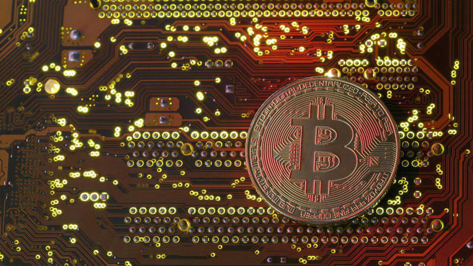 Una pieza de bitcoin delante de una placa base de un ordenador