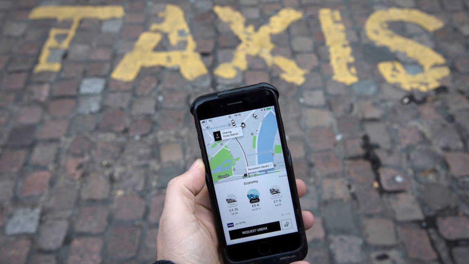 Un móvil con la aplicación de Uber abierta en una parada de taxis
