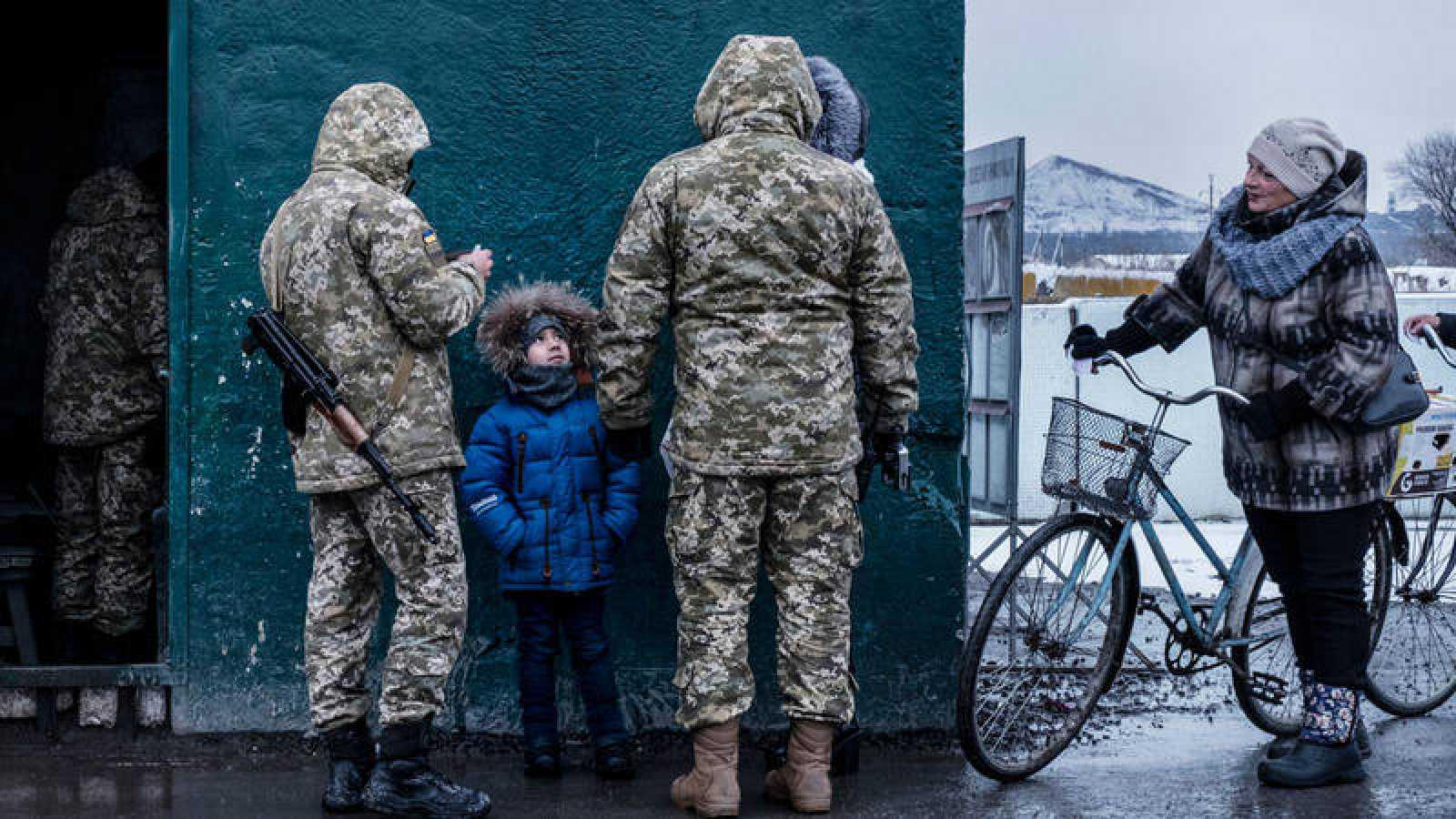 Un niño cruza un puesto de control supervisado por el ejército ucraniano