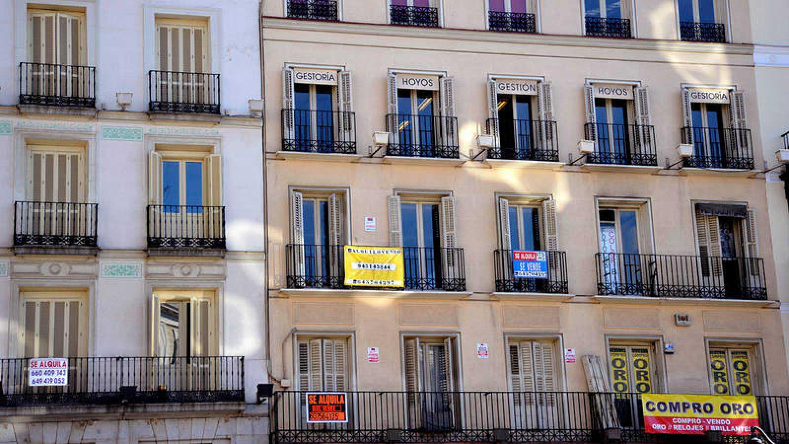Fachada de un edificio de la capital con diferentes carteles de alquiler y venta.