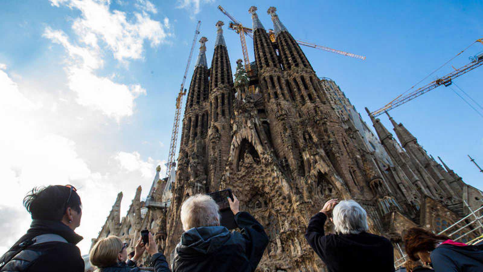 Un grupo de turistas fotografía la Sagrada Familia en Barcelona