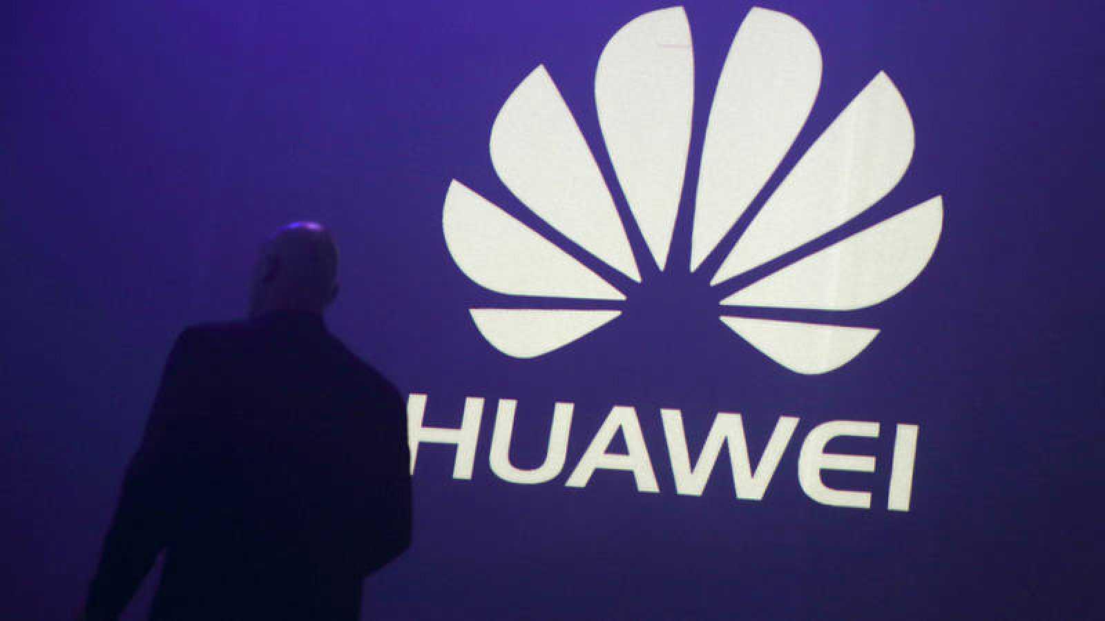 Un hombre pasa delante del logo de Huawei durante la presentación de un móvil de la empresa china
