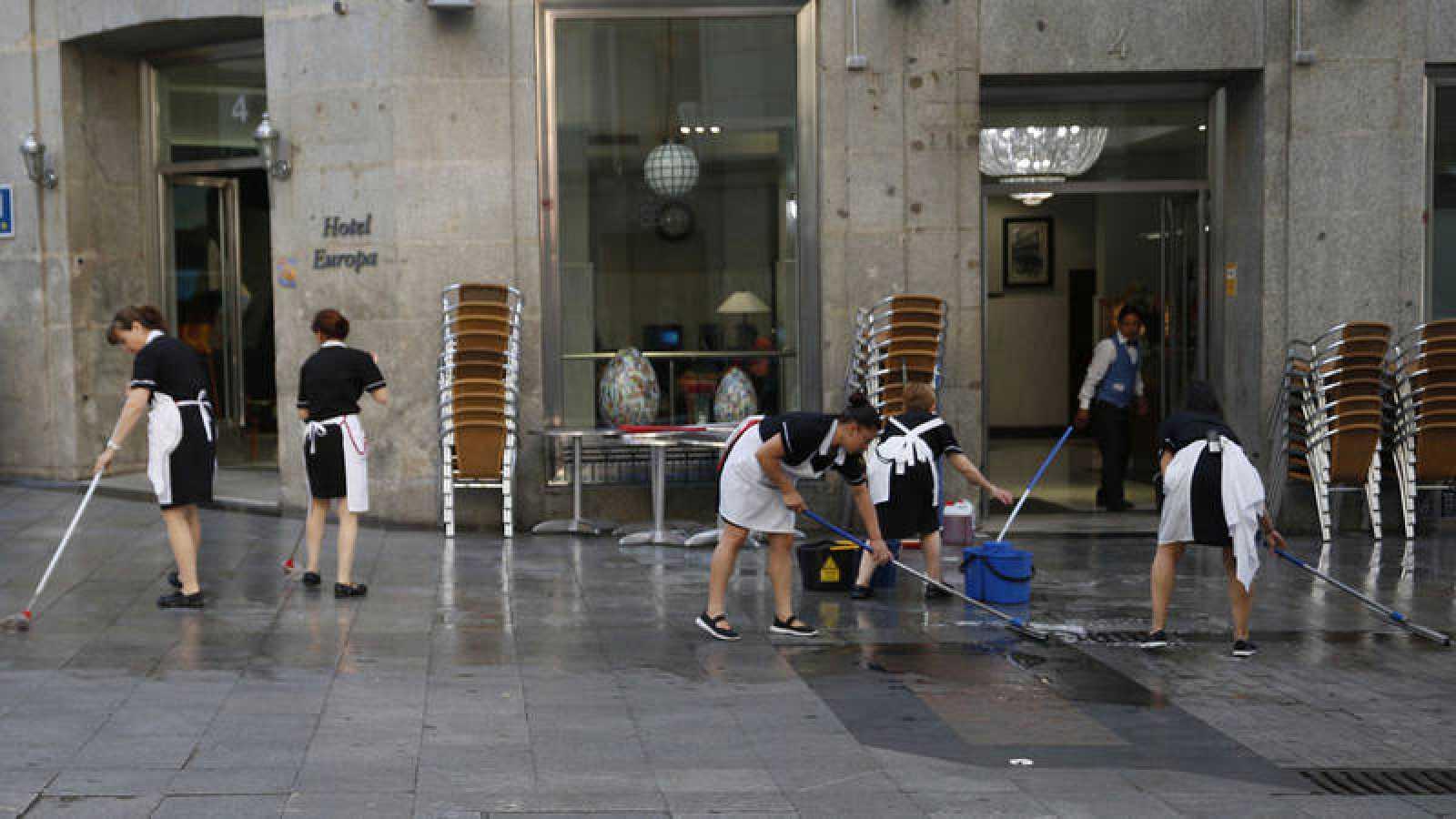 Un grupo de trabajadoras limpia la acera antes de montar la terraza de un hotel madrileño