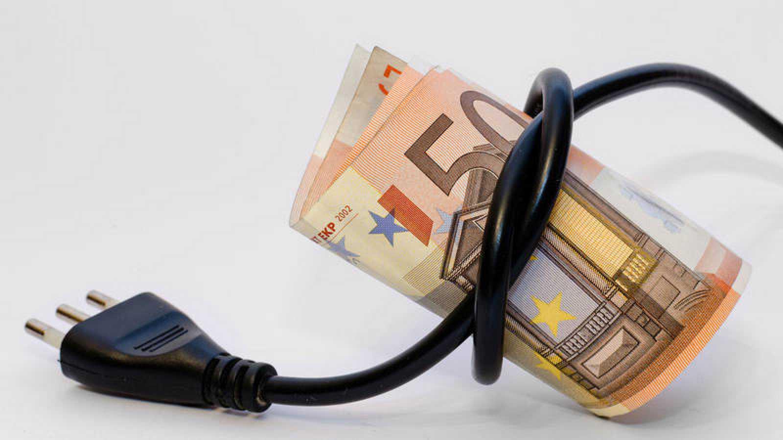 Un manojo de billetes de euros entrelazados con un cable eléctrico