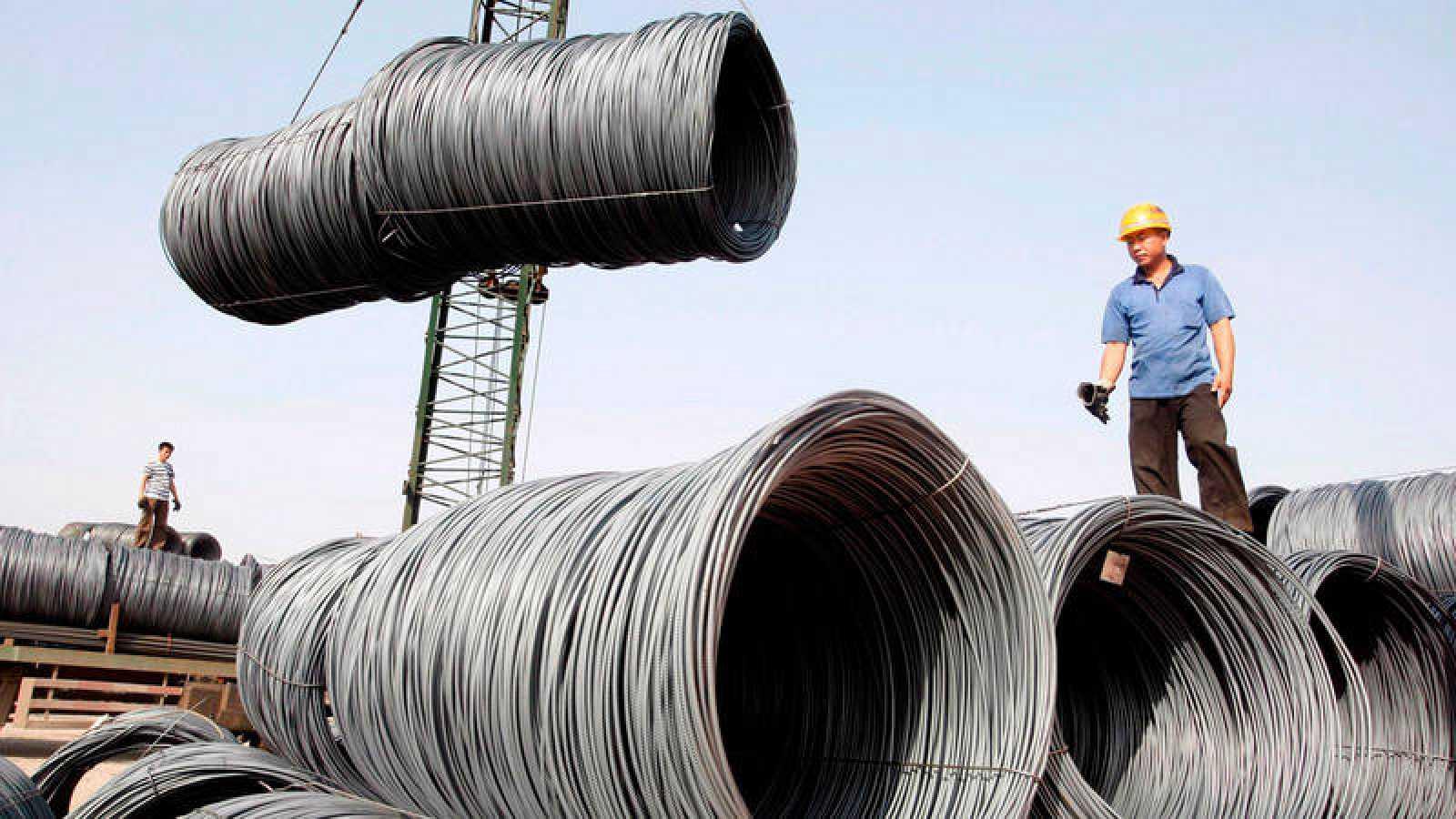 Operarios mientras transportan bobinas de cable de acero para su pesaje en Pekín (China)