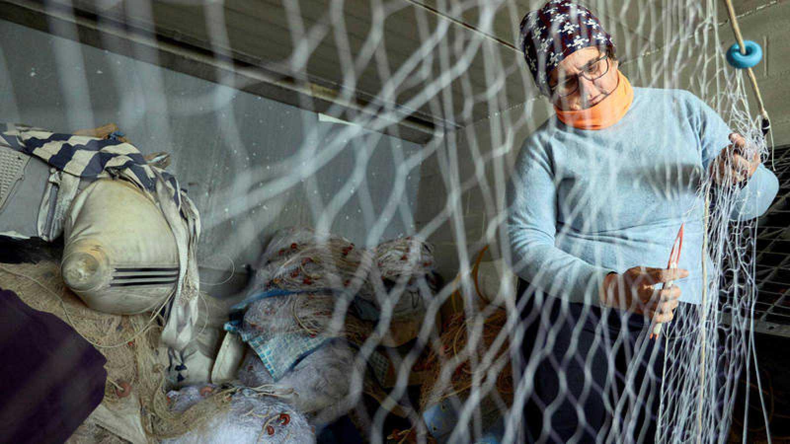 La presidenta de la asociación del mar del Grau de Gandia, mientras cose una red en la cofradía de pescadores